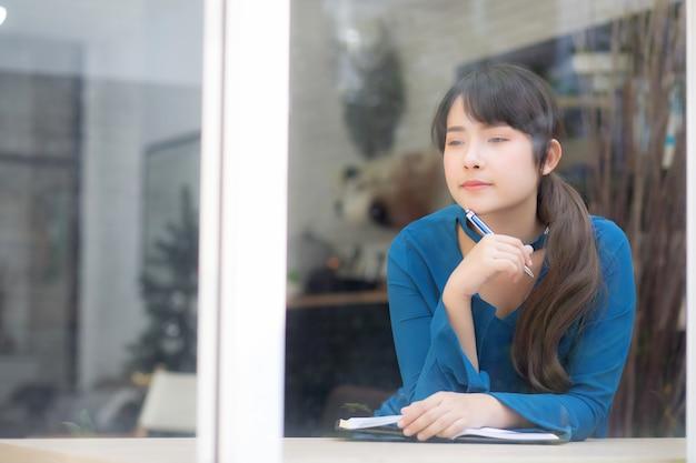Lächelnde denkende idee und schreiben der jungen asiatischen verfasserin des schönen porträts auf notizbuch