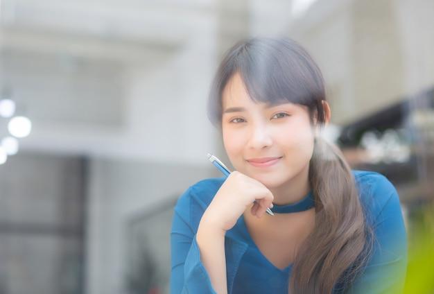 Lächelnde denkende idee und schreiben der jungen asiatischen verfasserin des schönen porträts