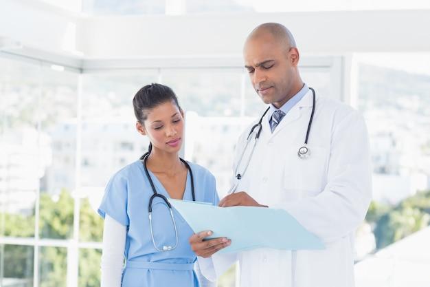 Lächelnde doktoren, die dateien lesen