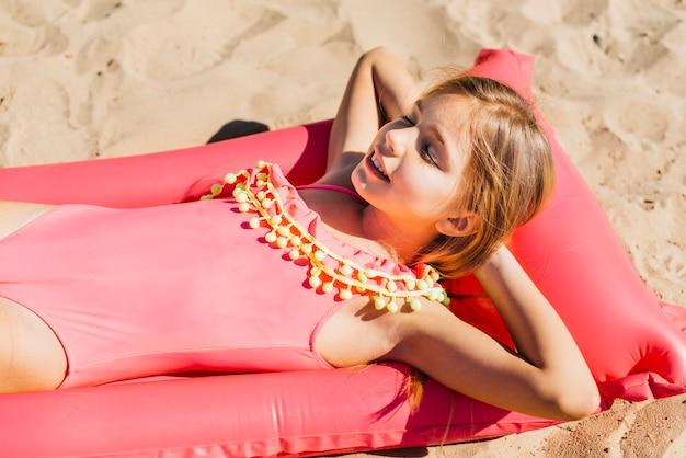 Lächelnde dünne mädchensonne, die auf farbe lilo auf sommerferien sich bräunt