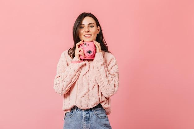 Lächelnde dunkelhaarige dame im stilvollen pullover wirft mit rosa kamera auf lokalisiertem hintergrund auf.