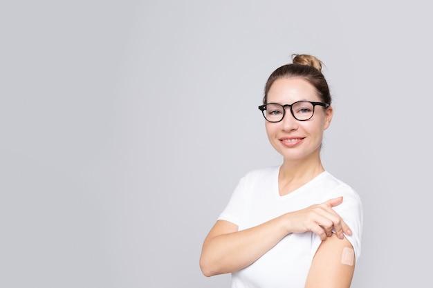Lächelnde echte frau mittleren alters mit einem pflaster oder pflaster auf der hand, die eine impfung erhält