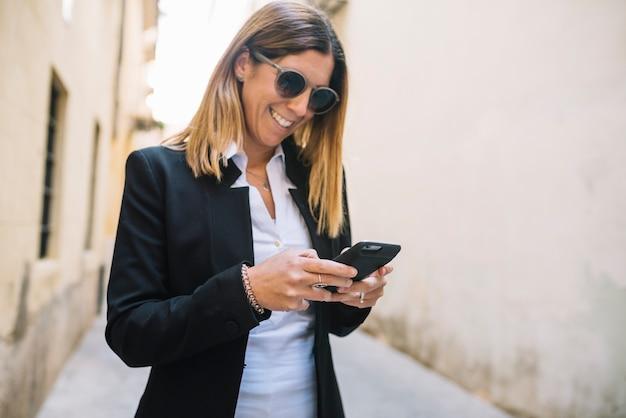 Lächelnde elegante junge frau, die smartphone zwischen gebäuden auf straße verwendet