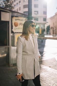 Lächelnde elegante junge frau mit sonnenbrille und smartphone auf straße