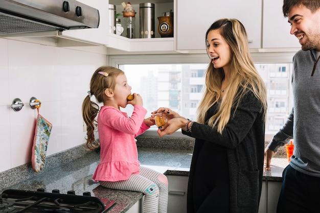 Lächelnde eltern, die ihre tochter isst kleinen kuchen in der küche betrachten
