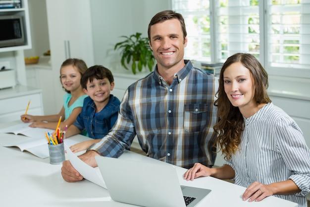 Lächelnde eltern, die mit laptop und kindern arbeiten, die im wohnzimmer zu hause studieren
