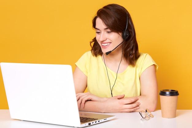Lächelnde energetische frau, die am schreibtisch mit verschränkten armen sitzt, headset hat und laptop-bildschirm, pappbecher kaffee betrachtet