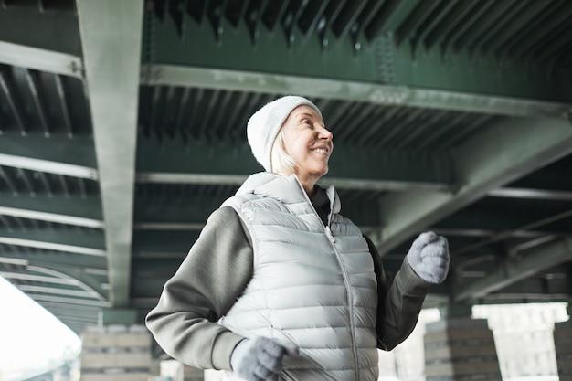 Lächelnde energische ältere kaukasische frau mit hut und handschuhen, die beim training im winter allein unter der brücke joggt