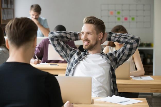 Lächelnde entspannende hände des mannes hinter dem kopf, der arbeit beim mitarbeiten genießt