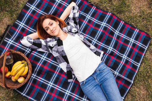 Lächelnde entspannte junge frau, die auf decke am picknick liegt