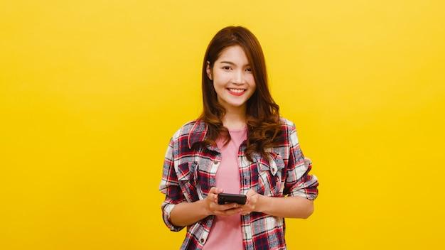 Lächelnde entzückende asiatische frau, die telefon mit positivem ausdruck verwendet, lächelt breit, gekleidet in freizeitkleidung und betrachtet kamera über gelber wand. glückliche entzückende frohe frau freut sich über erfolg.