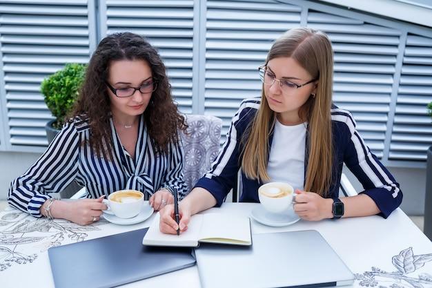 Lächelnde erfolgreiche arbeiterinnen arbeiten zusammen, arbeiten an einem laptop auf der terrasse, weibliche kollegen diskutieren ideen, mädchen in einem café bei einem geschäftstreffen. unternehmenskonzept