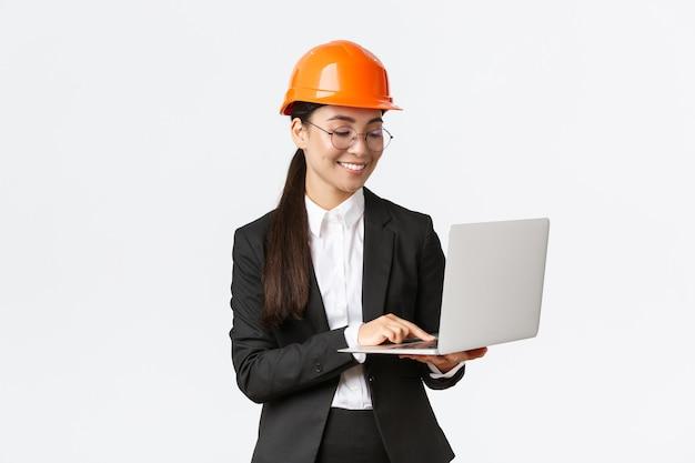 Lächelnde erfolgreiche asiatische wirtschaftsingenieurin, fabrikleiterin im schutzhelm