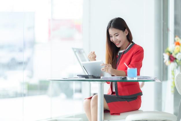 Lächelnde erfolgreiche geschäftsfrau des asiaten in der klage sprechend am telefon unter verwendung der tablette, die an sitzt