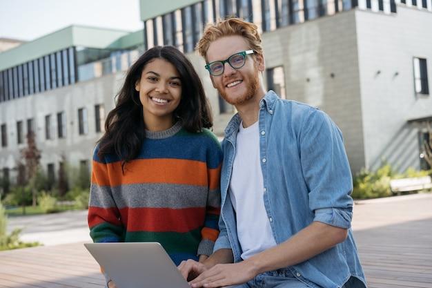 Lächelnde erfolgreiche geschäftsleute, die laptop verwenden, der zusammenarbeitet