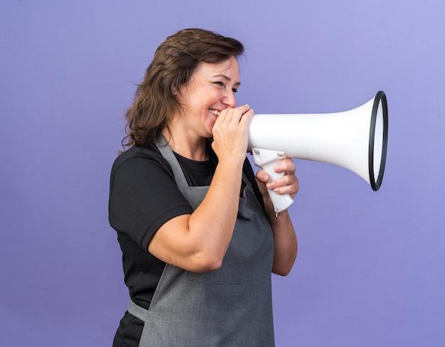 Lächelnde erwachsene friseurin in uniform, die einen lautsprecher hält und die seite isoliert auf lila wand mit kopienraum betrachtet