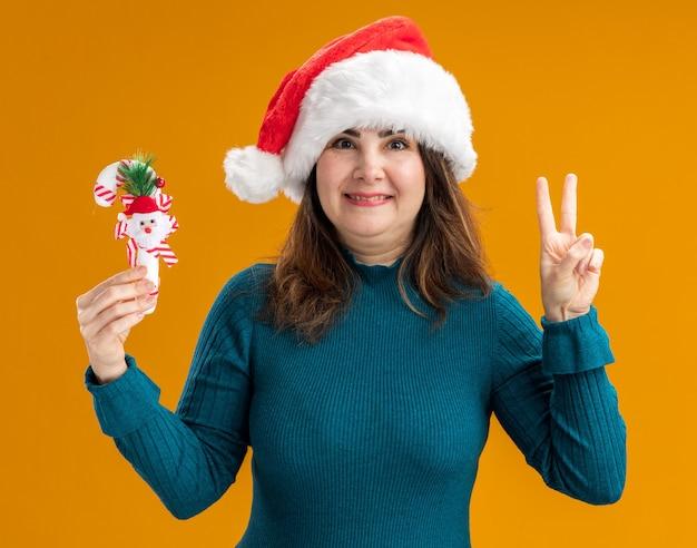 Lächelnde erwachsene kaukasische frau mit weihnachtsmütze, die zuckerstange und gestikulierendes siegeszeichen lokalisiert auf orange hintergrund mit kopienraum hält