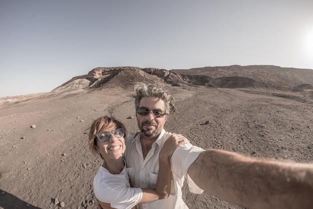 Lächelnde erwachsene paare, die selfie im nationalpark namib naukluft, reiseziel in namibia, afrika nehmen. fischauge, vintage-filter, getönt und entsättigt.