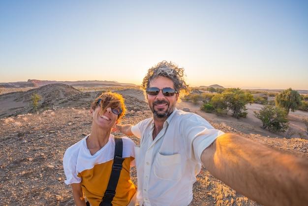 Lächelnde erwachsene paare, die selfie in der namibischen wüste nehmen