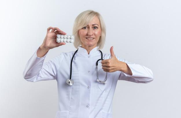 Lächelnde erwachsene slawische ärztin in medizinischer robe mit stethoskop, die medizintablette in blisterpackung hält und auf weißem hintergrund mit kopienraum nach oben greift