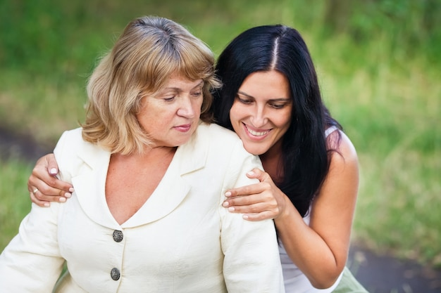 Lächelnde erwachsene tochter umarmt eine ältere mutter draußen in einem park