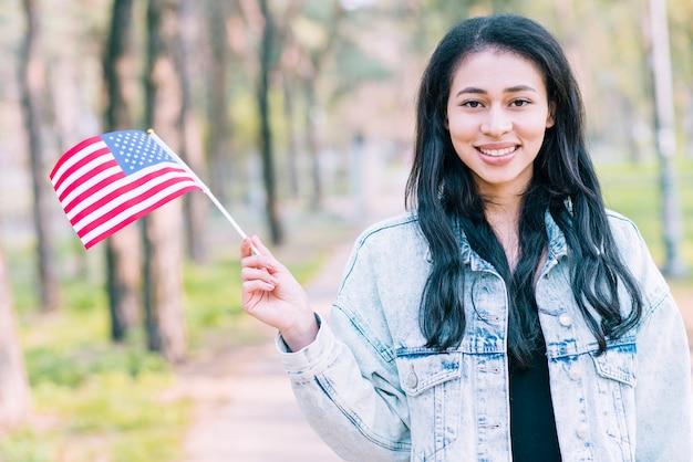 Lächelnde ethnische frau, die amerikanische flagge wellenartig bewegt