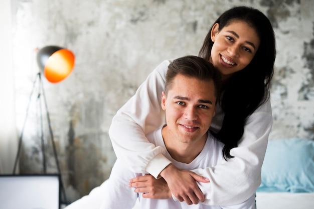 Lächelnde ethnische frau in der weißen kleidung, die gutaussehenden mann von hinten umarmt