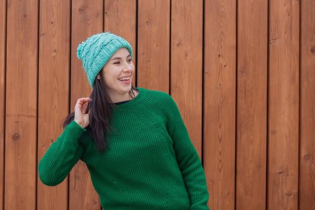 Lächelnde europäische frau im grünen pullover und im grünen hut auf hölzernem hintergrund. hochwertiges foto