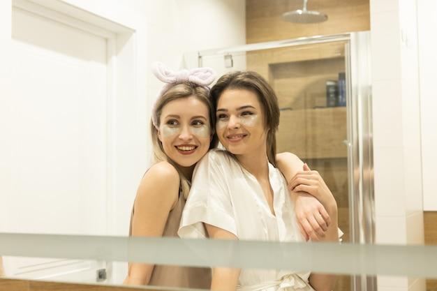 Lächelnde europäische freundinnen, die unter augenklappen auf ihren gesichtern suchen. junge schöne frauen im badezimmer. konzept der gesichtspflege. mädchenparty zu hause. innenraum der modernen wohnung