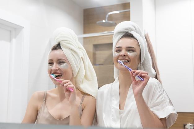 Lächelnde europäische mädchen, die zähne mit zahnbürsten putzen. junge frauen mit augenklappe im gesicht und eingewickelten badetüchern auf dem kopf. konzept der mädchenparty. innenraum des badezimmers in der modernen wohnung