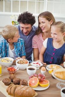 Lächelnde familie beim frühstücken bei tisch