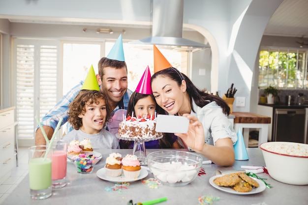 Lächelnde familie beim nehmen von selfie während der geburtstagsfeier