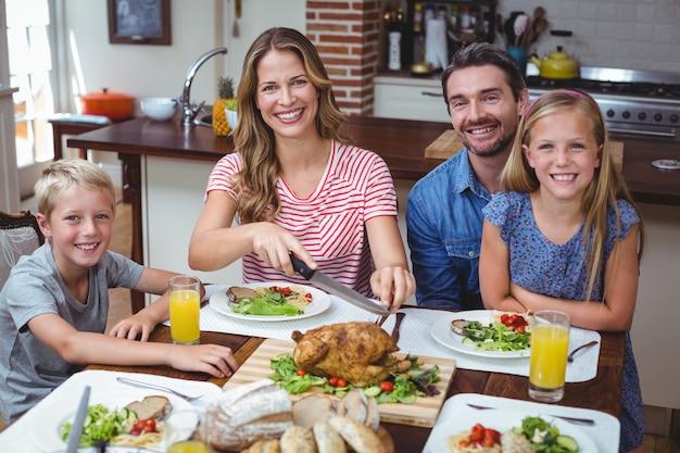 Lächelnde familie, die am speisetische sitzt