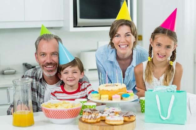 Lächelnde familie, die einen geburtstag zusammen in der küche feiert