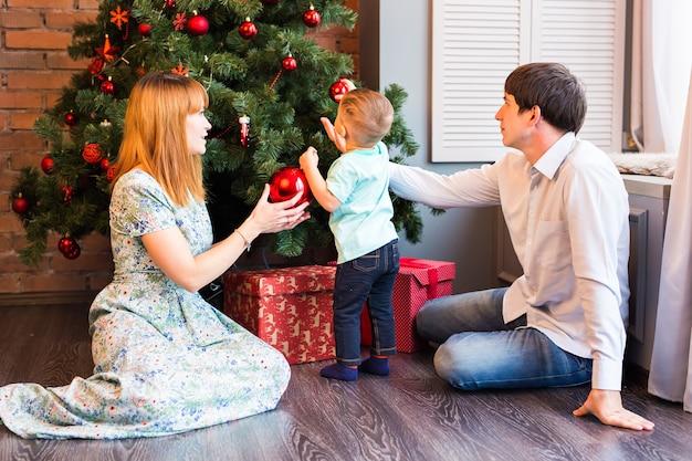 Lächelnde familie, die einen weihnachtsbaum im wohnzimmer verziert
