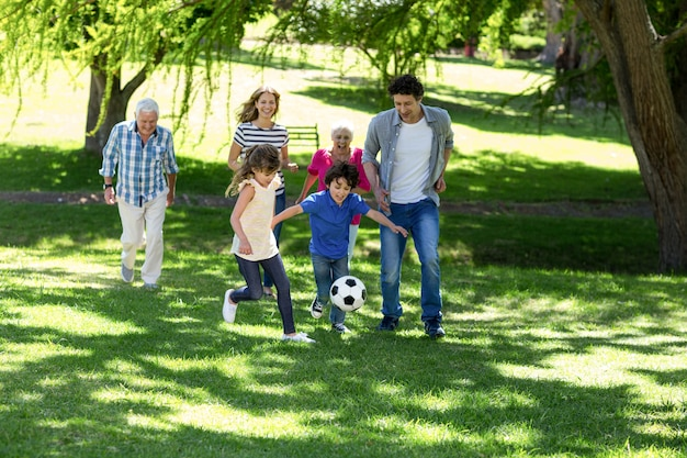 Lächelnde familie, die fußball spielt