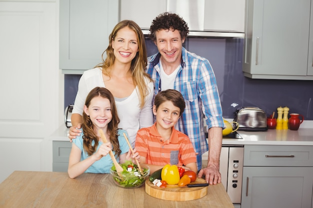 Lächelnde familie, die gemüsesalat zubereitet