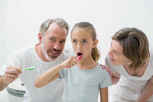 Lächelnde familie, die ihre zähne mit zahnbürste putzt