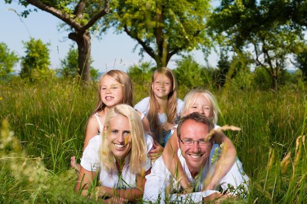 Lächelnde familie, die im gras im sommer liegt