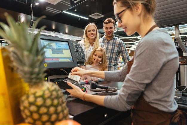 Lächelnde familie, die mit einer kreditkarte zahlt