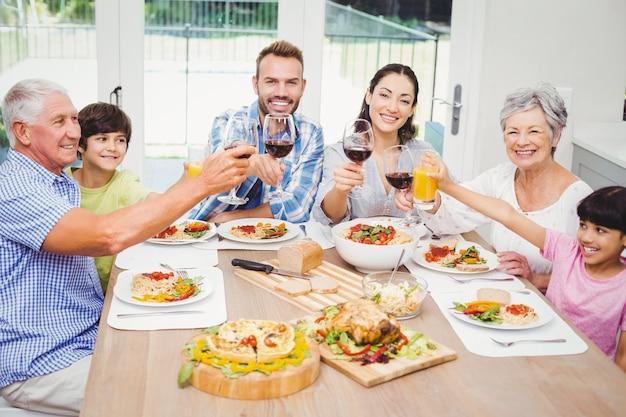 Lächelnde familie, die mit getränkgläsern klirrt