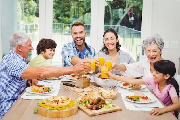 Lächelnde familie, die mit saftglas klirrt