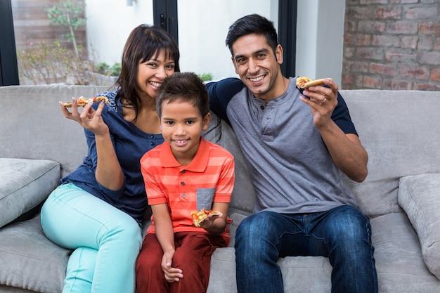 Lächelnde familie, die pizza auf dem sofa isst