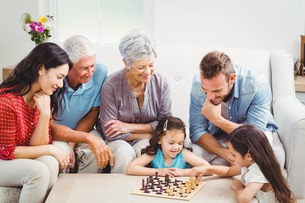 Lächelnde familie, die schach spielt