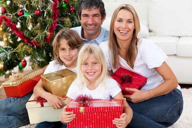 Lächelnde familie, die weihnachtsgeschenke hält