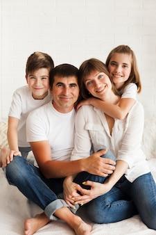 Lächelnde familie, die zusammen auf bett sitzt und kamera betrachtet