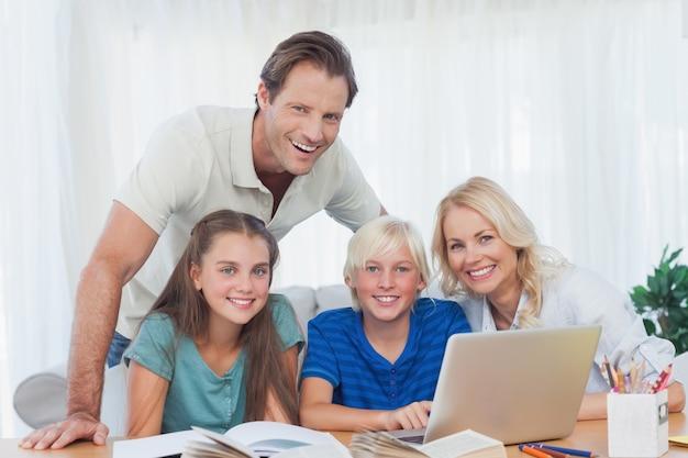 Lächelnde familie, die zusammen den laptop verwendet, um hausarbeit zu tun