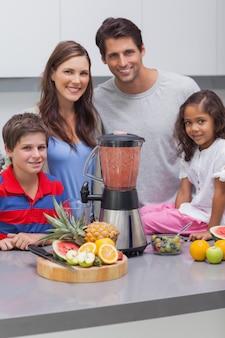 Lächelnde familie, die zusammen eine mischmaschine verwendet