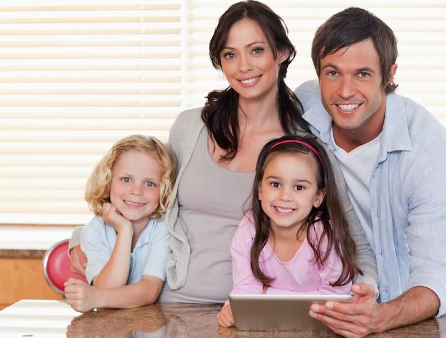 Lächelnde familie, die zusammen einen tablet-computer verwendet
