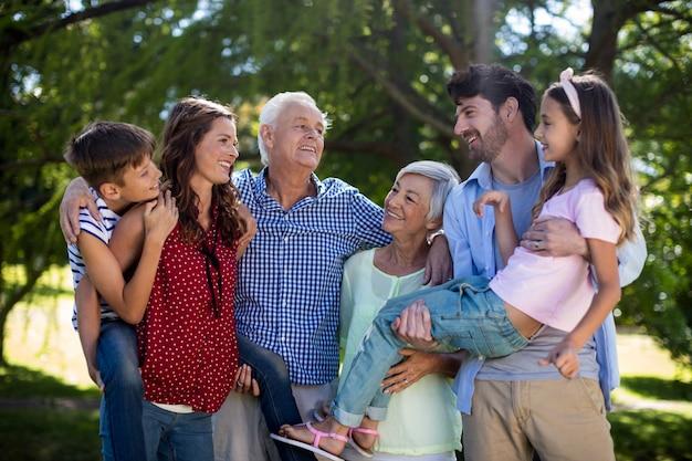 Lächelnde familie, die zusammen im park aufwirft